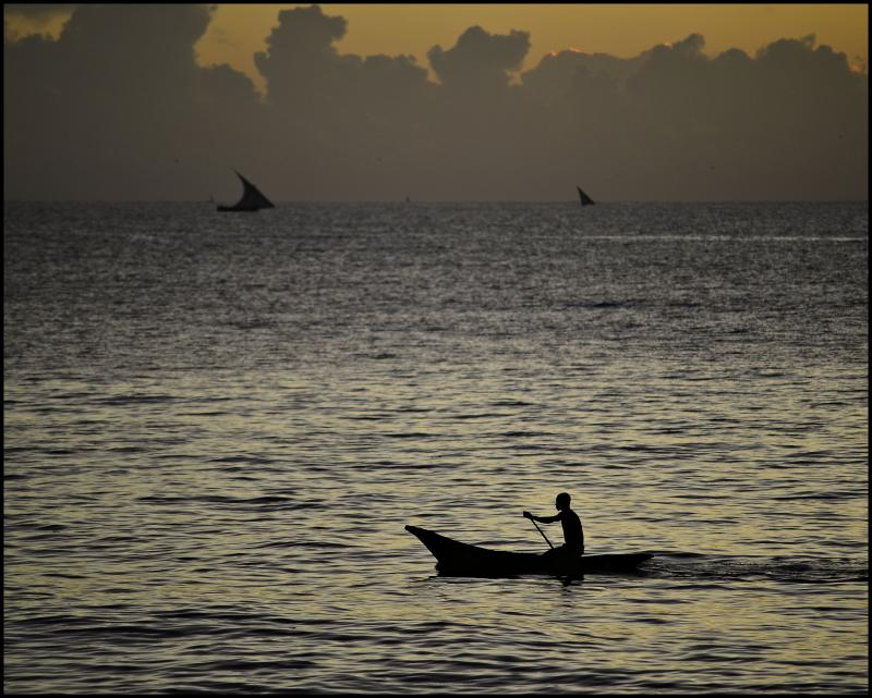 Fisherman taking his dugout canoe out at dawn, Dar es Salaam, Tanzania